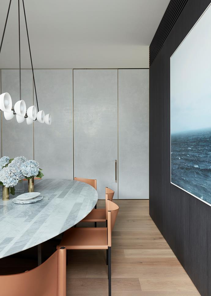 The dining area has a Salvatori 'Dritto' table and DePadova 'Rea' dining chairs, all from Boffi, under an Apparatus 'Trapeze 10' pendant light from Criteria. Artwork by Jerzy Michalski. Brass vases from Greg Natale. Wall panels in Rockcote Venetian plaster.