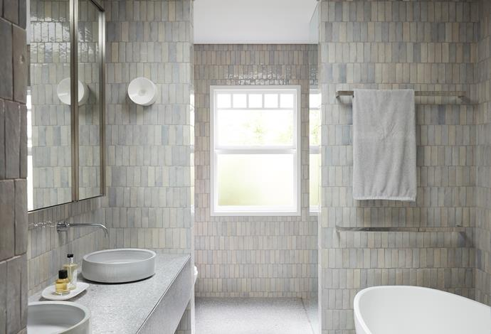 The ensuite bathroom has 'Casa Grey Chine' wall tiles from Onsite and Fibonacci Stone 'High Cloud' terrazzo floor tiles. White ceramic 'Anton' wall lights by Volker Haug.