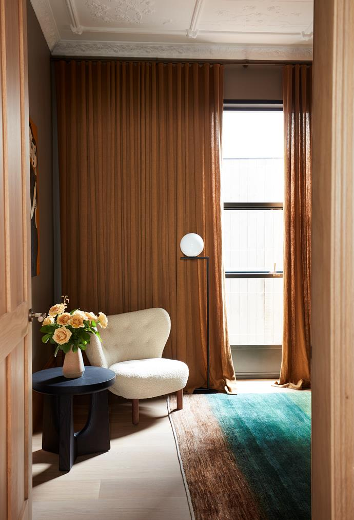The guest bedroom on the ground floor has a 'Little Petra' armchair from Cult and a Flos floor lamp by Michael Anastassiades from Euroluce. Curtains by Simple Studio.