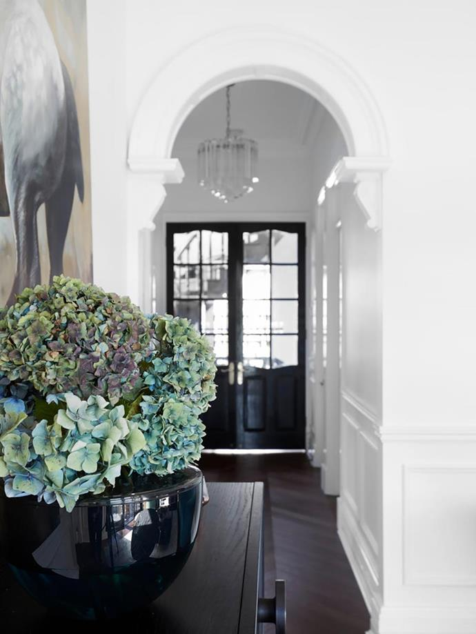 """Black french doors paired with European oak flooring are a glamorous touch in the monochrome hallway of this refreshed, [grand Sydney home](https://www.homestolove.com.au/grand-sydney-home-with-gorgeous-refresh-20706