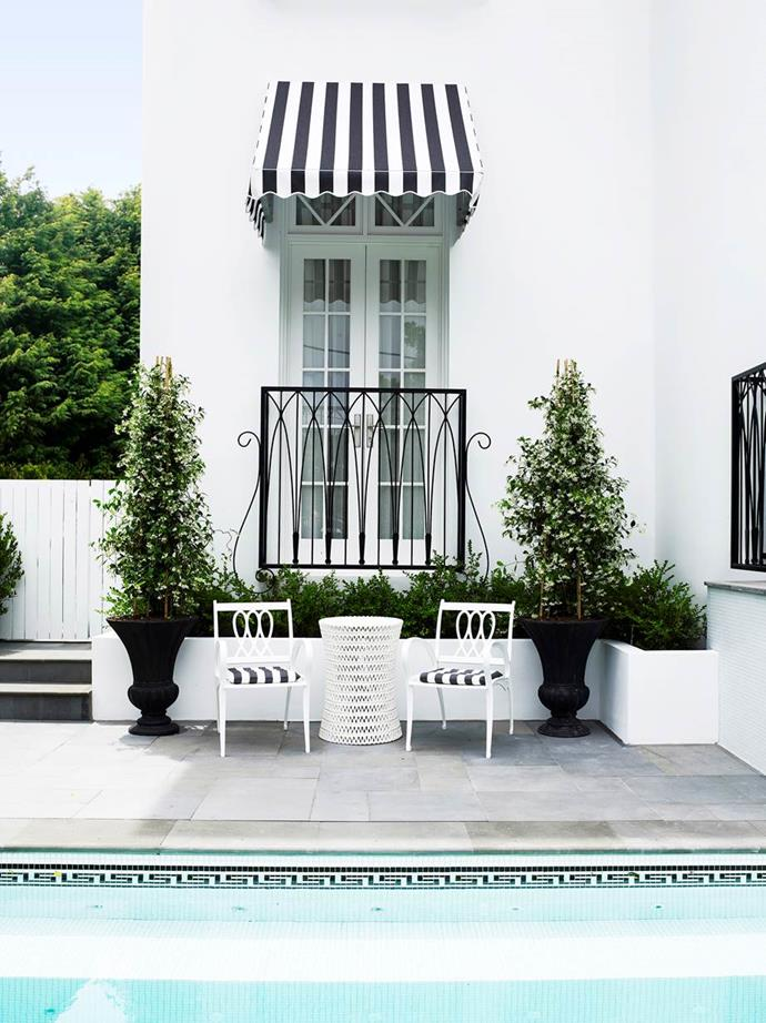 """A striped awning above a set of French doors opening to the pool area creates a very European look for this [luxurious Regency-style home](https://www.homestolove.com.au/gallery-emma-and-tonis-luxurious-regency-style-home-2311