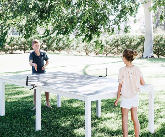 Two kids playing table tennis outdoors