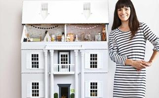 Woman wearing striped dress next to a large custom dollhouse