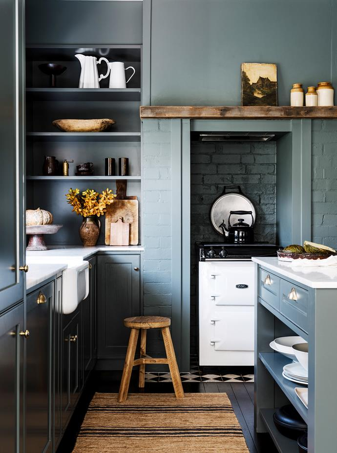 Electric stove, Aga Australia. Artwork on mantel, Found at Hepburn. Canisters and cutting boards, all vintage finds. White ceramics, Suzie Anderson Home. Wooden bowl, Water Tiger. Ceramic mugs, Planet. Fruit bowl, Orient House. Kettle, Le Creuse.