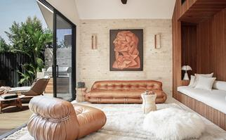 Timber living room with leather sofas and portrait of Shelley Craft (inset)