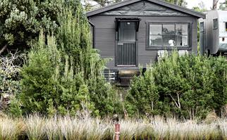 Exterior of a renovated black shack overlooking Lettes Bay in Tasmania