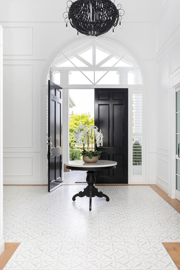 """Wainscoting is taken floor-to-ceiling in the grand entrance of [this Hamptons style new build](https://www.homestolove.com.au/waterfront-home-gold-coast-21855