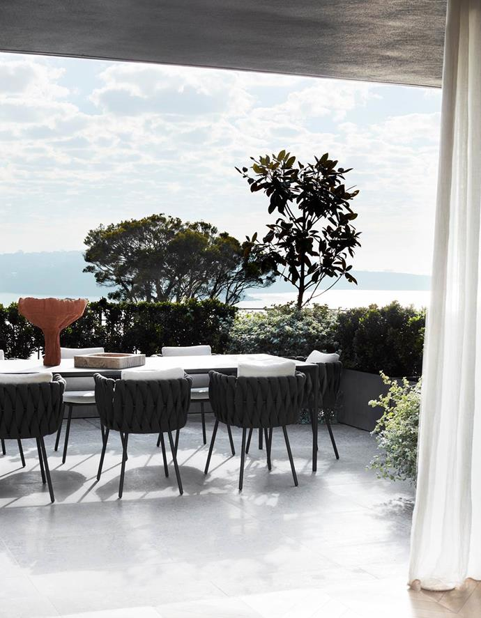 This alfresco dining area of this coastal home designed by Tahma Smith of Mrs Smith studio offers a front row seat overlooking Sydney Harbour. Linen curtains by Simple Studio create a soft filter separating the interior and exterior.