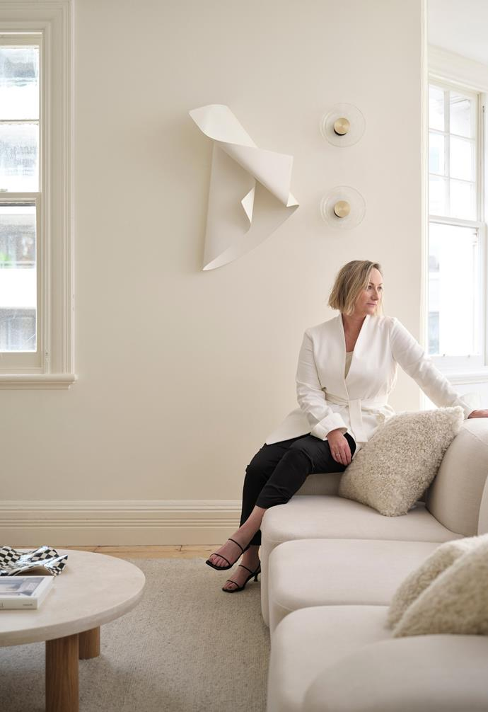 """""""I want guests to feel excited, inspired and comfortable and I want the apartment to appeal to all of their senses,"""" says Sarah Ellison. On the wall behind Sarah is a metal sculpture by The Visuals and lighting by ADesign. Works by both design studios feature throughout."""