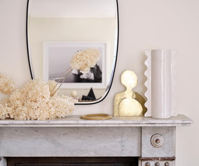 Mirrors from Life Interiors adorn several walls in the apartment, and here one of the mirrors gives a decorative display extra dimension. On the mantle is a beautiful golden sculpture by The Visuals, a Softedge Studio plate and a Sarah Ellison vase.