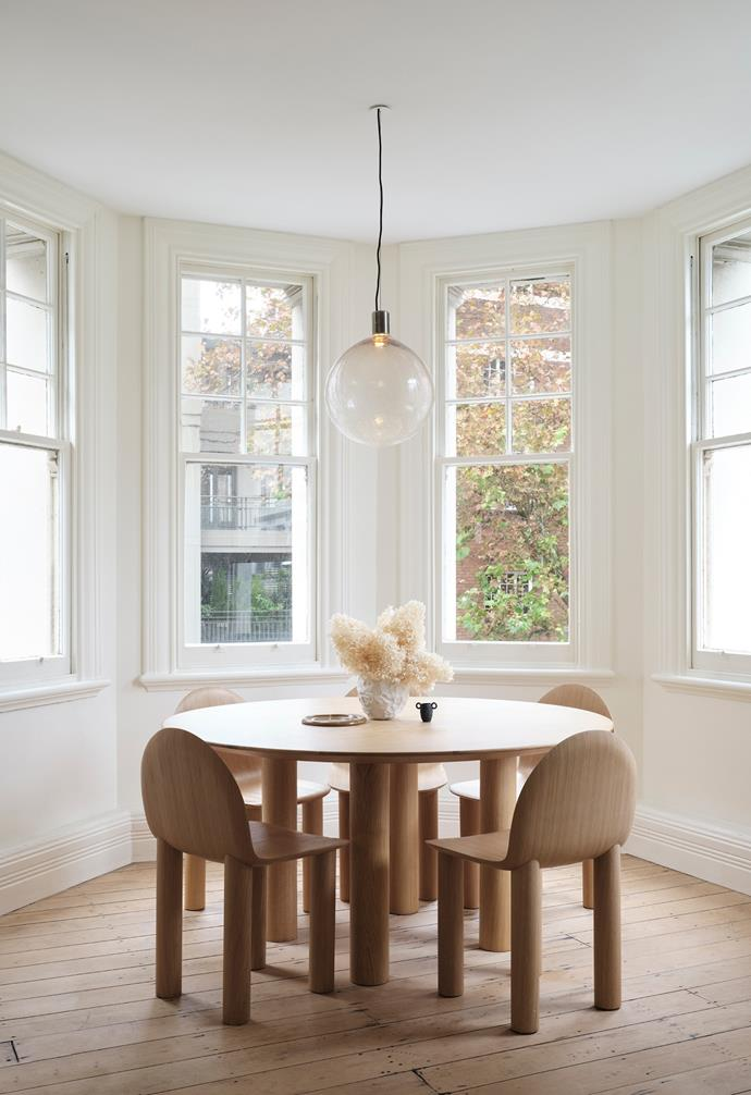 """Sarah's Earth dining table and Arch chairs beautifully sit within the curved contours of the Art Deco apartment. The pendant is by ADesign. Rather than mixing colours, Sarah layers different tonal textures and materials. Chrissi adds, """"I love the depth of thought placed into each of her designs. The furniture has visual definition."""""""