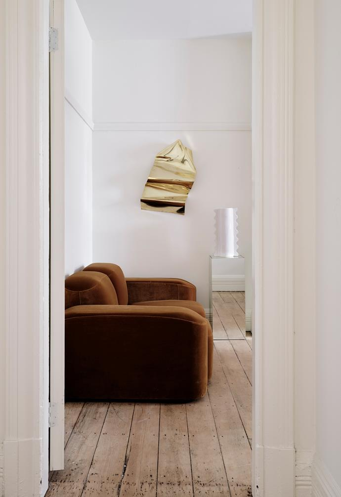 """Framed by this doorway is the Muse sofa in caramel velvet, the Royeré vase and a tall mirrored plinth, all by Sarah. The sculptural work on the wall is by The Visuals. """"We used velvet upholstery for its luxe appeal in the caramel colourway as it felt in line with the Deco colour palette,"""" Sarah explains."""