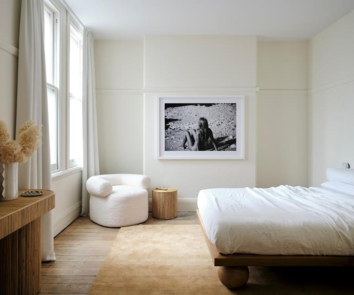 """In one of the three bedrooms is a covetable Sarah Ellison-designed Yoko bed and Huggy chair. Supporting acts include her rattan Halston console and Freddie side table. Sarah says she loved curating the art and chose """"classic and timeless"""" Akila Berjaoui black and white photography for the apartment """"to add old world charm"""". She also installed three canvas artworks by Saxon Quinn, who is represented by Saint Cloche, alongside metal sculptures by The Visuals."""