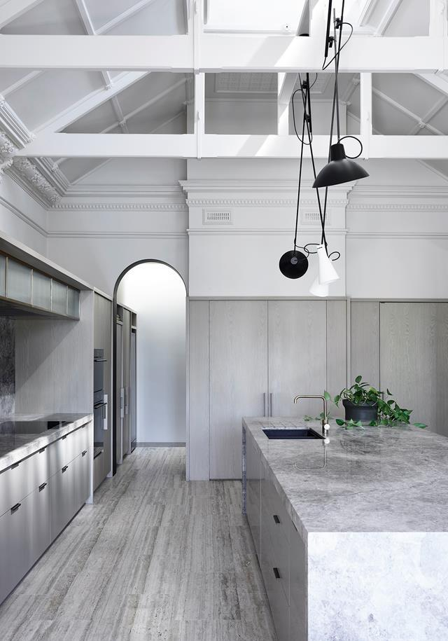 """This [Victorian villa's](https://www.homestolove.com.au/victorian-villa-restoration-22891/ target=""""_blank"""") old but completely reimagined kitchen is in an icy palette of silver travertine, stainless steel and grey walls. Likely once functioning as a games room, vast industrial ceiling beams overlook the kitchen island bench where a billiards table once stood. The island bench is made from Persian travertine and Grey Tundra stone from Peraway Marble."""