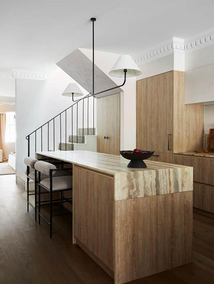 """A bespoke iron pendant light by Phoebe Nicol hangs above the island bench in this [French-inspired home's](https://www.homestolove.com.au/elegant-home-french-inspired-interior-sydney-22184/ target=""""_blank"""") timber and limestone kitchen. The island cabinetry is in oak veneer topped with a benchtop in travertine from Gitani Stone."""