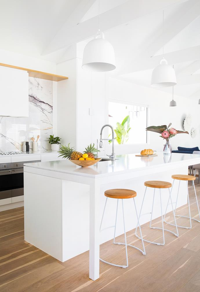 """Integrated Miele appliances and custom-made oak veneer cabinetry painted in Resene Double Alabaster create a streamlined look in the kitchen. The Smeg rangehood was enveloped in a white timber box with a shelf of American oak to frame the [splashback](https://www.homestolove.com.au/splashback-finishes-4432 target=""""_blank""""). """"Although it cost more, we wanted to use real marble – it's the focal point of the space,"""" says Danielle of the New York marble from WK Designer Stone."""