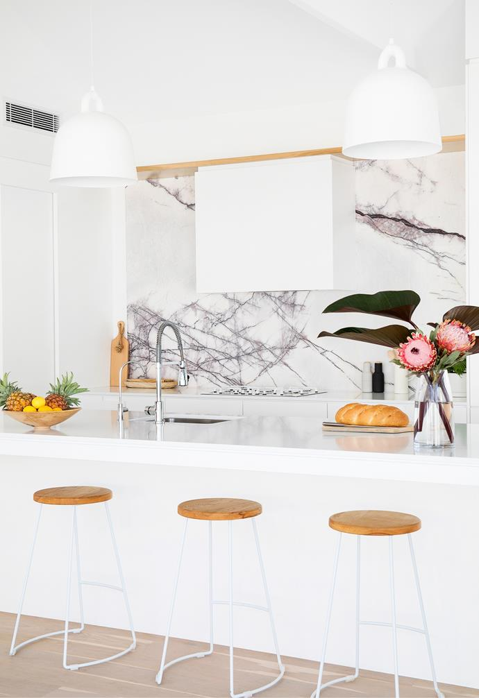 A pair of Normann Copenhagen 'Bell' lamps sourced from Surrounding Australia above the Matt Ultra White reconstituted stone island define the zone. Reece fittings, including a Teknobili pull-out mixer, make washing up in the deep Franke sink easy, while a Mizu Drift offers filtered water on tap.