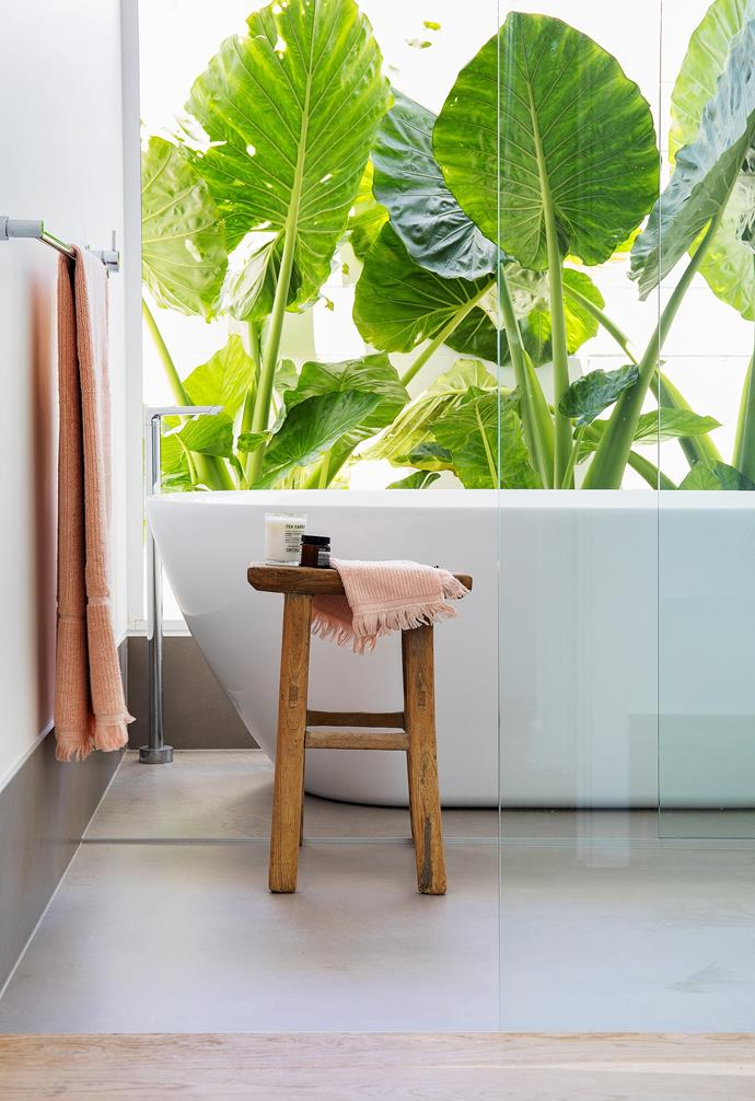 """With a view out to lush tropical giant elephant ear plants, the main bathroom has a resort-like vibe that makes it almost feel like it is outdoors. """"We chose neutral finishes which wouldn't date,"""" says Danielle of the white walls and Quantum Six Nuovo Concrete matt floor tiles. The [freestanding bath](https://www.homestolove.com.au/freestanding-bath-design-ideas-4520 target=""""_blank""""), paired with Milli 'Glance' floor bath outlet, both from Reece, are a classic choice, while the pretty pink towels from The Beach People add a splash of colour."""
