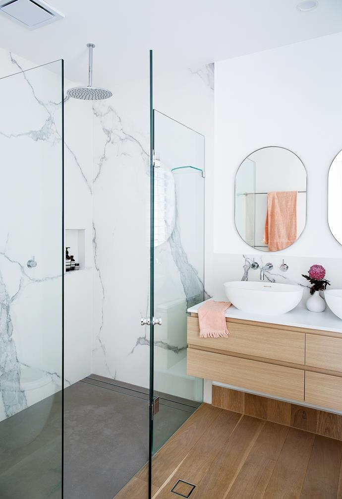 """To avoid the irksome job of cleaning grout, Nick opted for large marble-look sheets in the ensuite. """"Because of the sheer weight of them, manoeuvring and installing them was one of the most difficult aspects of the build, but it was worth the effort,"""" he says. Quantum Six Nuovo Concrete matt floor tiles, also from WK Designer Stone, pick up the grey veining of the walls. The same marble-look wall tile in a smaller format was carried through to the vanity splashback, which features a custom floating vanity reflecting the timber tones of the Mafi oak floors."""