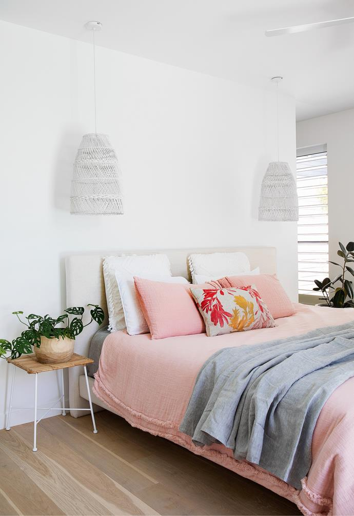 """Knowing how Navah loves to snuggle in their bed and with another child on the way at the time, Nick and Danielle decided to invest in comfort for the whole family and had a super king bed made by MuBu Home. """"The size of the room meant we could get something quite large and it's a luxury we all appreciate,"""" says Nick. Linen from Adairs adds a feminine touch, with a Bonnie And Neil 'Banksia' cushion providing a dash of pattern. In keeping with the more natural rattan bedside tables from Adairs, chic pendant lights set to dimmers create a soft ambience after dark."""