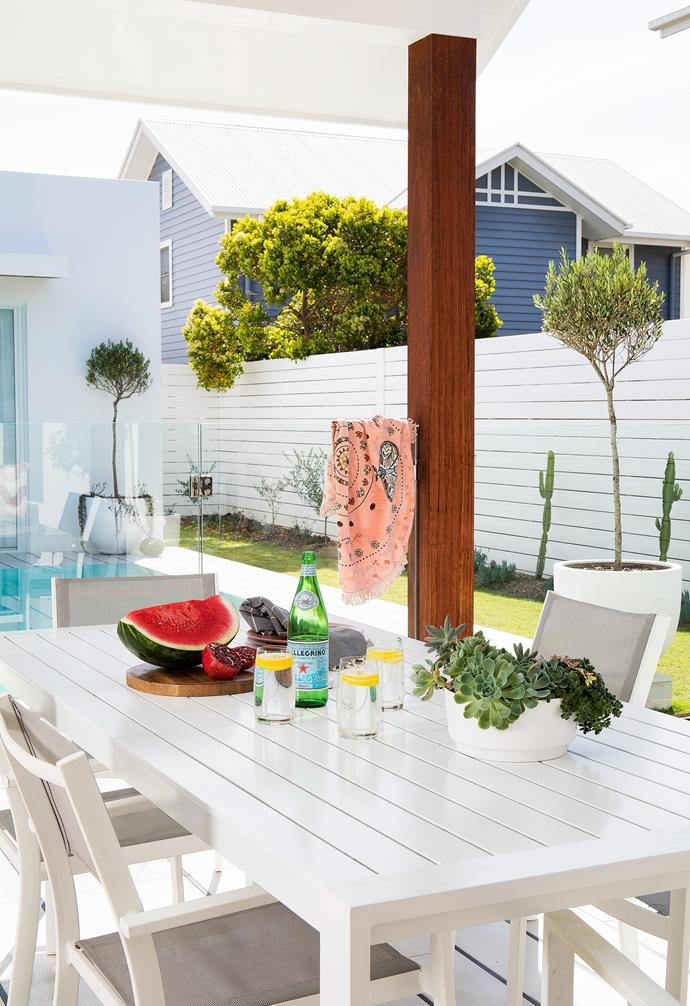 """Weekends are usually spent outside, at the beach, in the pool or relaxing in the outdoor area. """"Being undercover, the outdoor area can be used no matter what the weather is like and, even when you're not in the pool, it's lovely to look at the water,"""" says Danielle. An outdoor dining setting from Freedom and timber fencing painted in Resene Double Alabaster make for a serene white space. Large pots from The Balcony Garden feature olive tree topiary from a local nursery who cared for them during the 10-month build."""