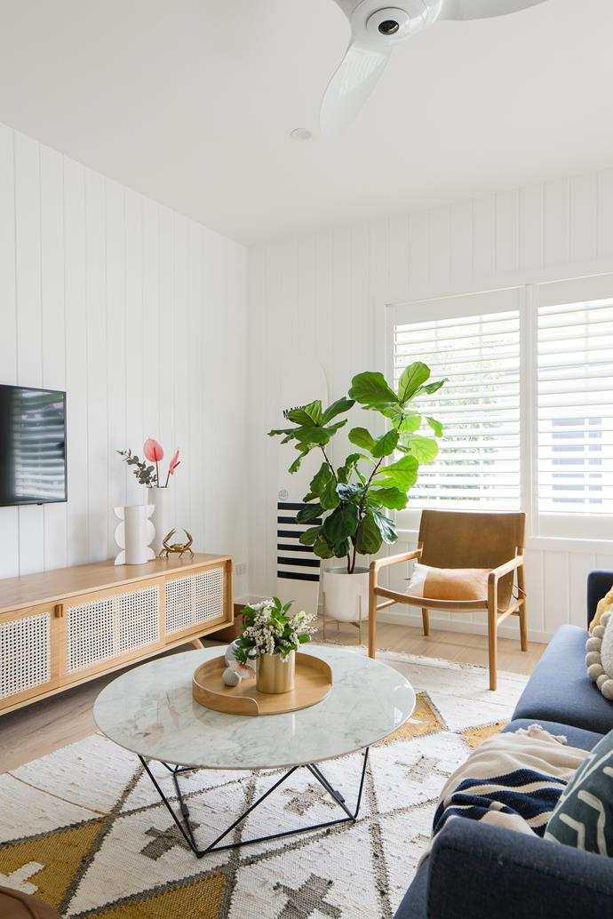 """A flourishing fiddle leaf fig adds a homely touch, while a handcrafted wooden surfboard hints at the wonders outside, in the living room of this [backyard cottage retreat on Sydney's Northern Beaches](https://www.homestolove.com.au/cottage-rental-renovation-northern-beaches-22423 target=""""_blank"""")."""