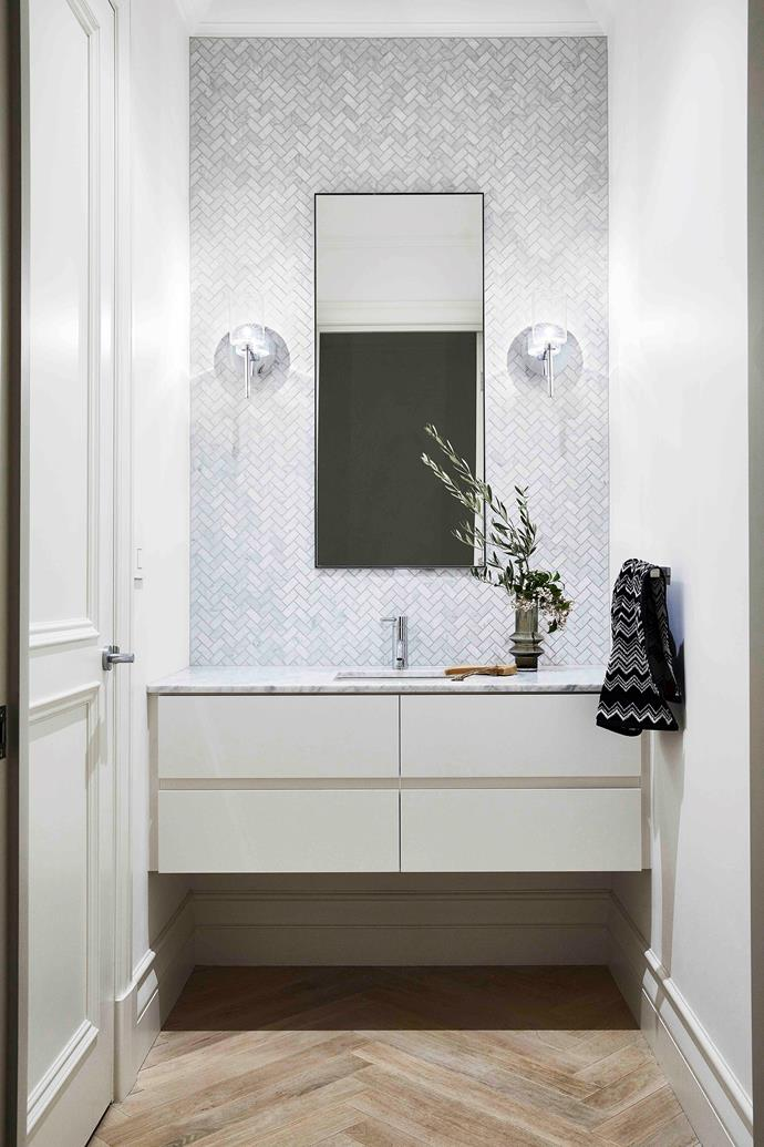 """Herringbone 'Bianco Carrara' marble mosaic tiles pack a tactile punch in the powder room of this [Spanish-style home in bayside Melbourne](https://www.homestolove.com.au/modern-spanish-style-home-melbourne-21563