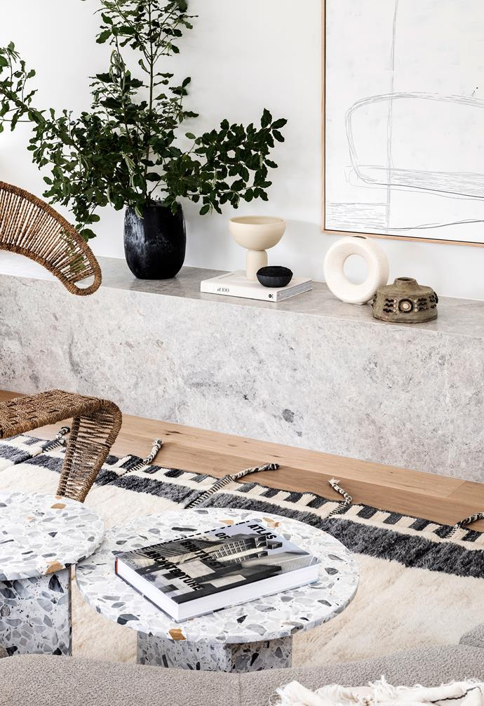 """Lauren wasn't afraid to use premium stone and stone-based materials in zones the kids would frequent, selecting a large block of Tundra Grey marble for this shelf and bench in the living room. The two terrazzo coffee tables were designed and made by Lauren's firm, [Built by Wilson](https://builtbywilson.com/