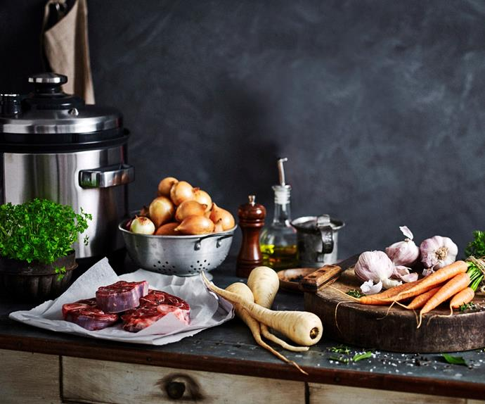Fresh vegetables on a table next to an electric pressure cooker