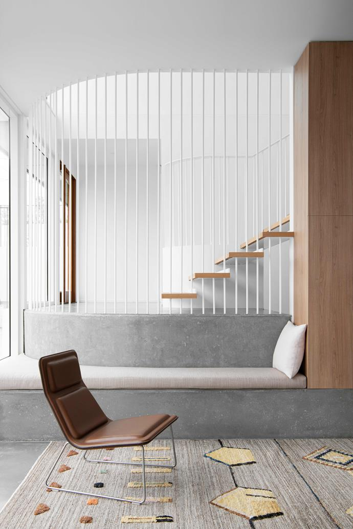 Detailing with thin metal rods has created what looks like a sheer textured curtain around the stairs. The result is child-roof yet wonderfully open. On the lowest level is a built-in seat.