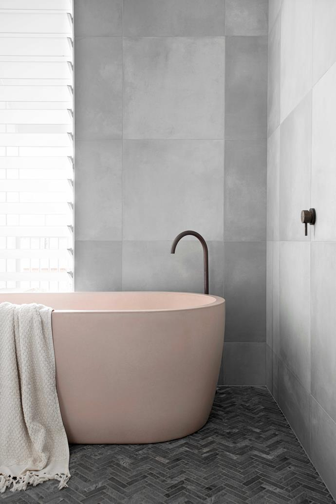 """""""We bought the wall tiles from  a local supplier, with a natural-stone herringbone tile for the floor,"""" says Katrina of the main bathroom design. Bath, [Concrete Nation](https://www.concretenation.com.au/