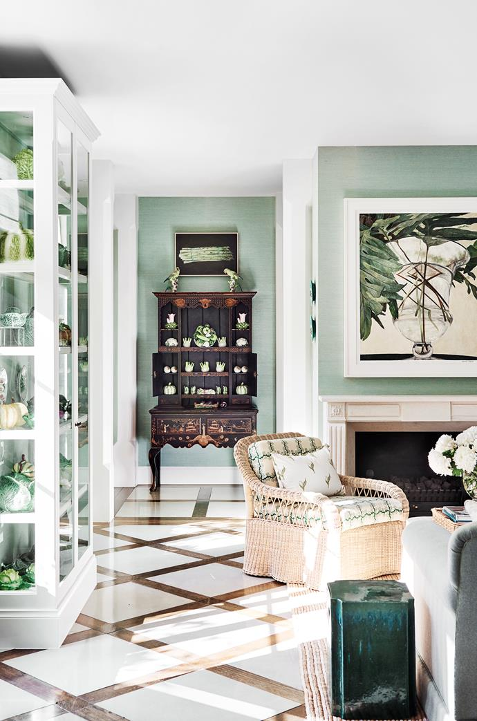 Cane chair with seat cushions covered in 'Espalier Square' fabric in Emerald from Soane. Ceramic stool from Orient House. Cressida Campbell artwork above mantelpiece. A Kevin Lincoln artwork hangs above the cabinet made to display the client's china collection of 30-plus years sourced from different eras and countries. Antique George I-style chinoiserie dresser from The Vault Sydney. Abaca woven rug from International Floorcoverings.