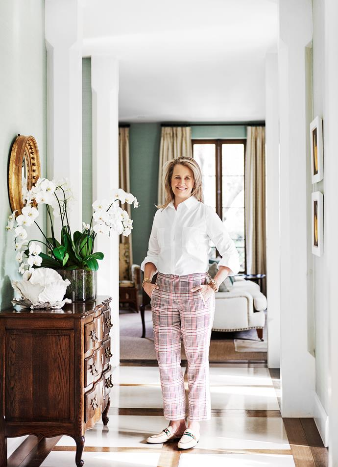 Interior designer Adelaide Bragg stands in the hallway beside an antique console on which sits a white ceramic cabbage by Vladimir Kanevsky.