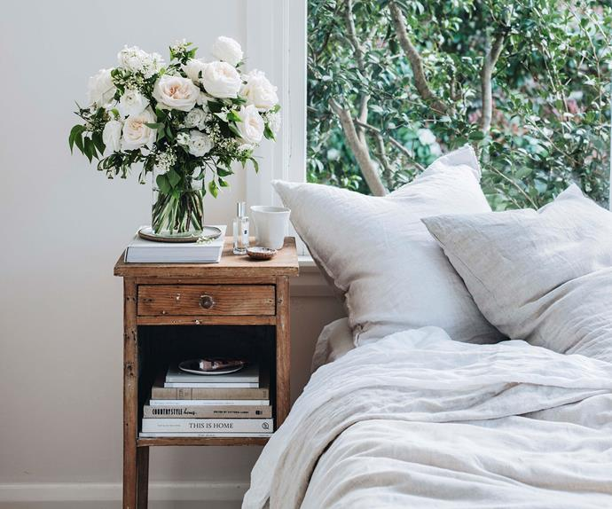 Bedroom with a vintage timber bedside table topped with freshly arranged flowers