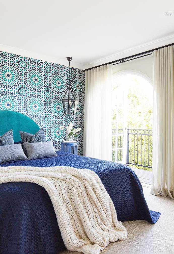 """The last room to be completed in the renovation project, Hugh and Susie's bedroom shines in vibrant jewel tones. 'Nasrid Palace Mosaic' wallpaper in Aegean from Orient House combined with 'Belmont' lanterns from Emac & Lawton honours the Mediterranean influences of the home. A bedhead upholstered in luxurious Schumacher velvet in Teal from Orient House was designed by Woods & Warner and built by H&J Furniture, while velvet cushions take the pattern game up a notch. """"We had worried initially that the vibrancy of colour may not be conducive to a relaxing room, but it turned out to be really peaceful,"""" says Susie."""