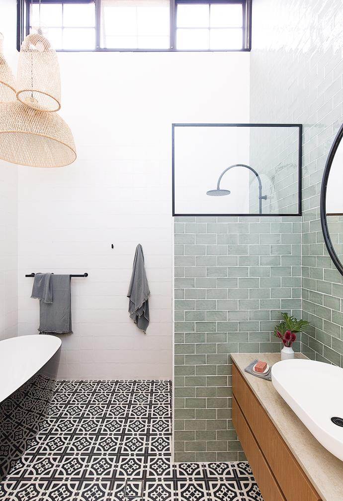 The glossy Kado 'Lure Petite' freestanding bath and black and white 'Zaragoza' encaustic floor tiles from Teranova Tiles anchor the bathroom in bold monochromatic fashion, while black accessories and tapware and an 'Onyx' mirror from Warranbrooke punctuate the scene.