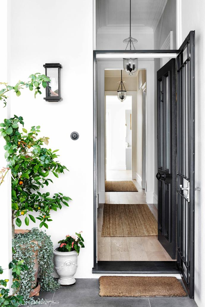"""The front door is painted Dulux Domino, with a matching steel security door from [Kings Security Doors](https://www.kingssecuritydoors.com.au/ target=""""_blank"""" rel=""""nofollow""""). Pendants, [Pearl Lighting & Brassware](https://www.pearllighting.com.au/ target=""""_blank"""" rel=""""nofollow""""). On the verandah, a rambling rosebush and potted cumquat tree bring a hint of country charm to the inner-city street."""