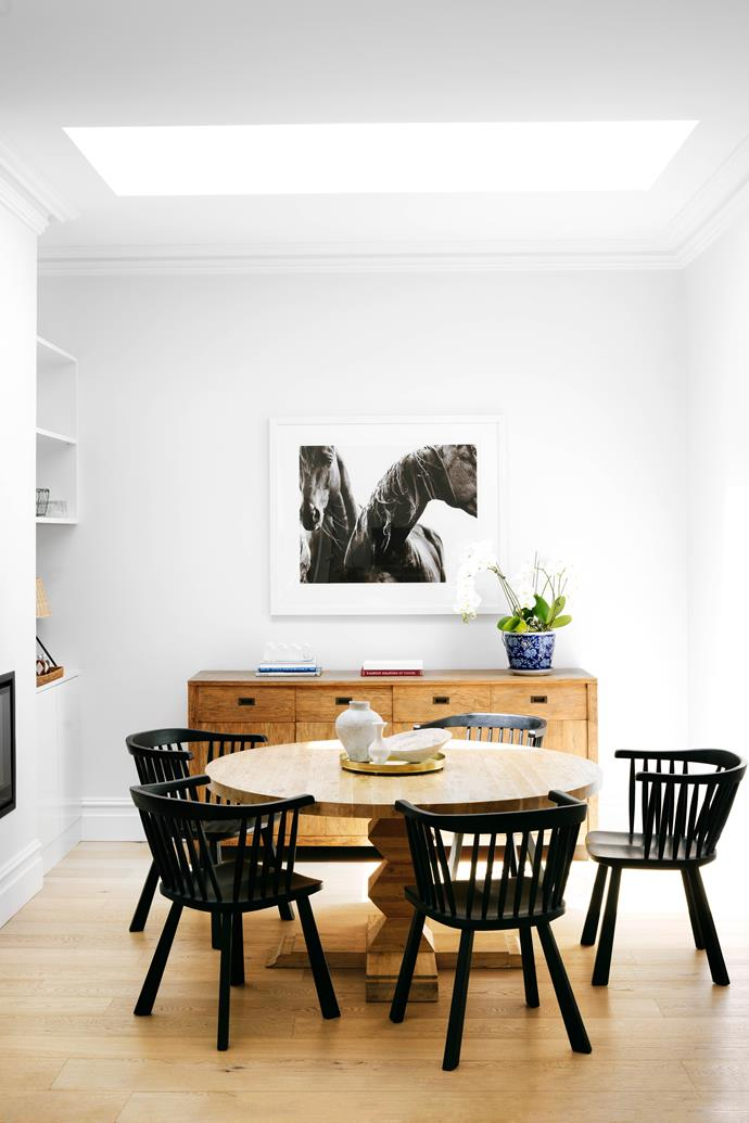 """A very large skylight was installed in the centre of the space, over the family's St Tropez oak dining table from [MCM House](https://www.mcmhouse.com/ target=""""_blank"""" rel=""""nofollow""""). Gas fire, [Escea](https://www.escea.com/au/ target=""""_blank"""" rel=""""nofollow""""). Timber sideboard, [Coco Republic](https://www.cocorepublic.com.au/ target=""""_blank"""" rel=""""nofollow""""). Framed photograph from the Wild Brumbies series by [Nick Leary](https://nicklearycollections.com/ target=""""_blank"""" rel=""""nofollow""""), who's a friend of the family."""