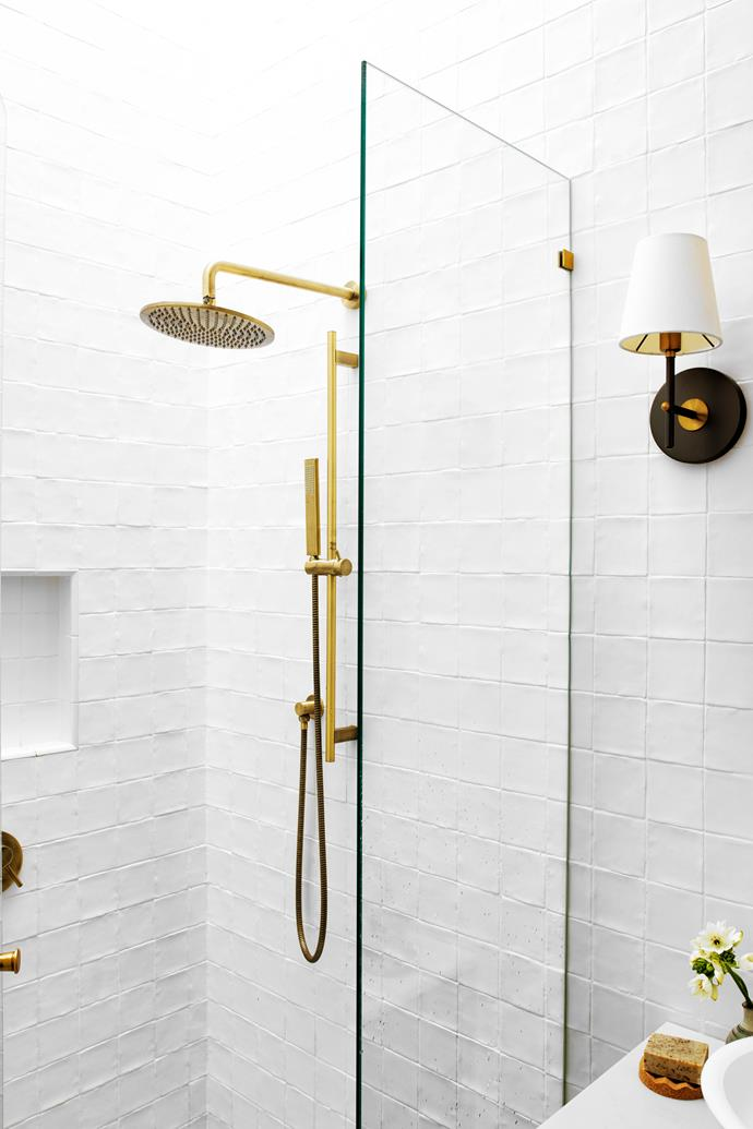 """Tucked behind a frameless glass divider are a rain shower and tapware from [ABI Interiors](https://www.abiinteriors.com.au/ target=""""_blank"""" rel=""""nofollow""""). Wall lamps, [Pearl Lighting & Brassware](https://www.pearllighting.com.au/ target=""""_blank"""" rel=""""nofollow"""")."""