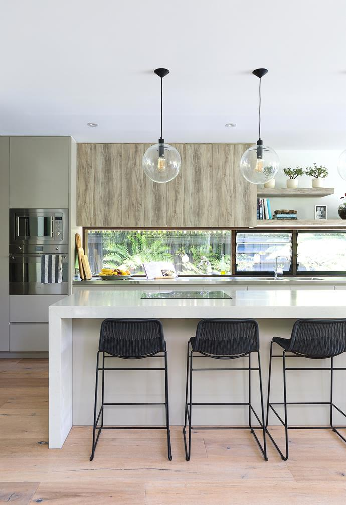 """The couple splurged on the impressive island – which has an 80mm waterfall benchtop in Caesarstone London Grey 5000 – and an integrated Smeg induction cooktop to maximise interaction. The sumptuous Navurban timber-veneer cupboards and base cabinets in Dulux Dune lend a contemporary beachside look, while the black rattan stools from Feelgood Designs provide colour contrast. Architect Ramon designed the window splashback: """"It not only provides light, but visually links to the front of the house and the view outside, making the area feel like less of a work station,"""" he says."""