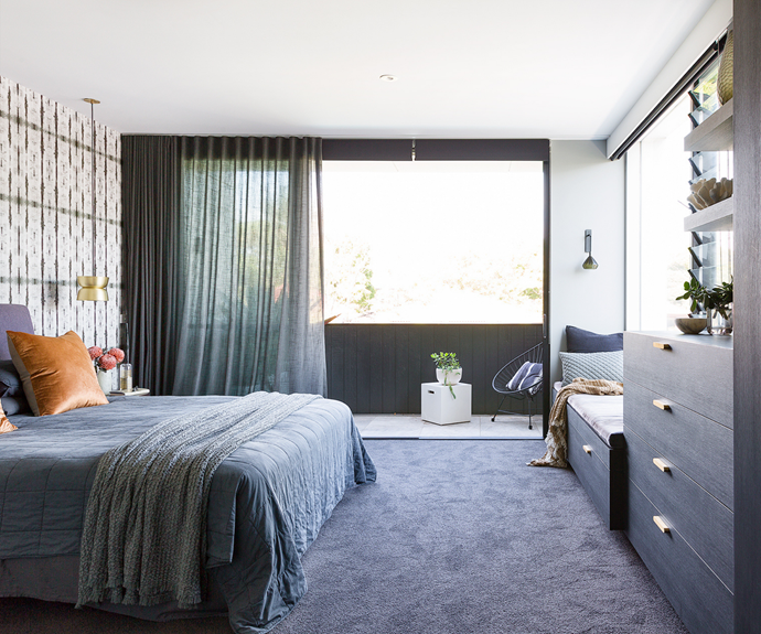 """""""A high-end, luxe hotel was my vision,"""" says Pippa, who admits she would have never tried a dark and moody 'grown up' space without interior designer Melissa – who chose the Shibori 'Stalactite' wallpaper to bring the room to life. """"It pops, but it's still in keeping with the rest of the aesthetic,"""" says the designer. Cushions, a blanket and a throw rug from Maison Et Jardin create sophisticated softness on the bed, while the Auhaus 'Pinch' pendant above the bedside table and an Articolo 'Ici' wall sconce on the back wall add extra wow. Joinery in Navurban pre-finished timber veneer is made all the more glamorous by Auhaus 'Humble HO3' brass handles."""