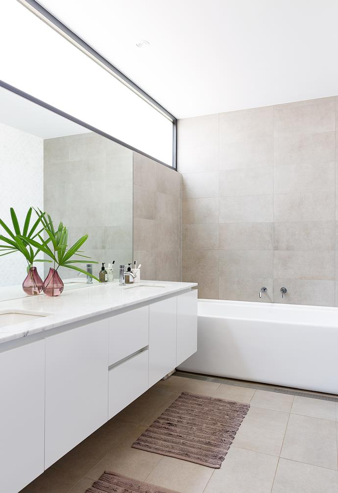 The sense of luxe continues in the main ensuite, which features underfloor heating, sumptuous materials and a Caroma 'Cube 1800' freestanding bath, big enough for the whole family. A double vanity was a must-have – the 20mm Carrara marble benchtop was sourced from CDK Stone and paired with some sleek Rogerseller Tonic basin mixers. 'Stoneclay' tiles in Cendre from Signorino Tiles create a continuous flow from floor to wall.