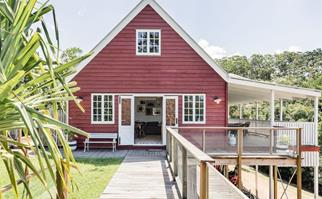 Exterior of red barn-style house on stilts with timber deck