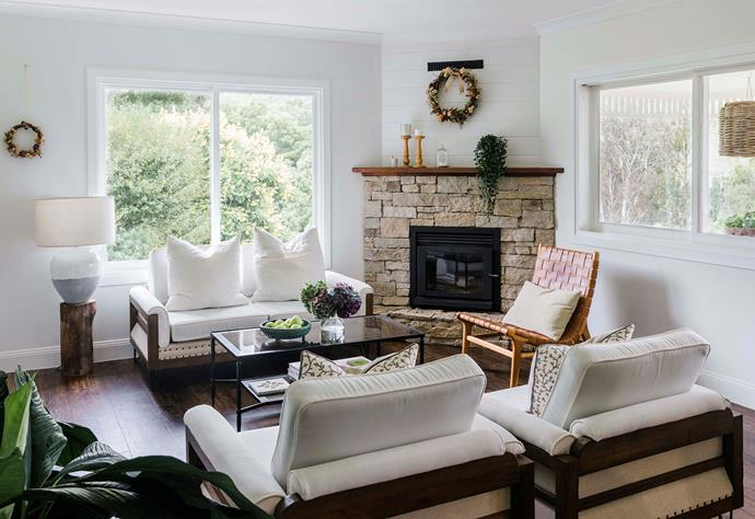 A stone fireplace dominates the well-lit lounge room.