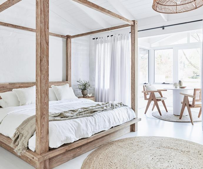 """Main Bedroom: Suzy and the team of owners wanted to imbue this huge space with a sense of luxury and escape, so she included a sunroom with views of the plunge pool and land beyond. The timber four-poster bed, side tables and pendant light are all custom. Bed linen, In Bed. Braided round jute rug, [Miss Amara](https://missamara.com.au/collections/miss-amara-collection