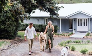 Brick farmhouse in background with a couple and a pony and dog in the foreground