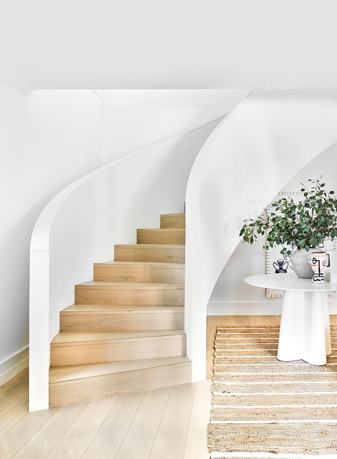 The sculptural curved staircase wows at the front door. Forster dining table and vases, Oz Design Furniture. Stoneware side table, House of Orange. Maitai rug, Freedom.