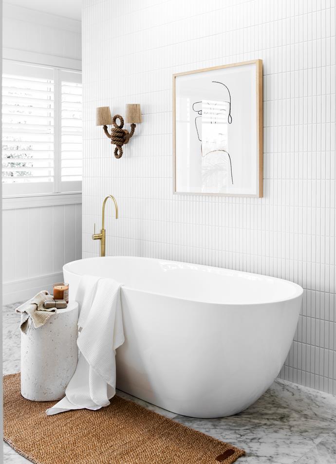 Bath, tapware, all Reece. Carrara-look floor tiles and Kit Kat feature wall tiles, all TileCloud. Hermes side table, CLO Studios. Russes wall light, The Society Inc. Floor mat, The Dharma Door. Artwork, Lounge Lovers.