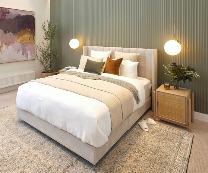 Master bedroom with green corrugated feature wall and upholstered bed head