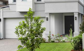 Grey home with white garage door and tidy front lawn